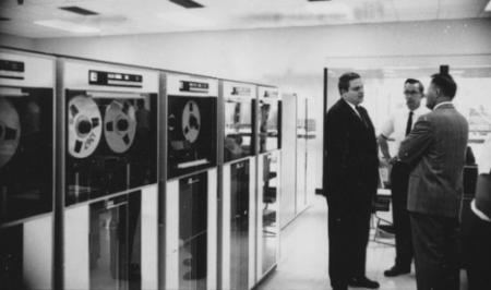 Three men conversing in front of an old data-processing room that uses tape.