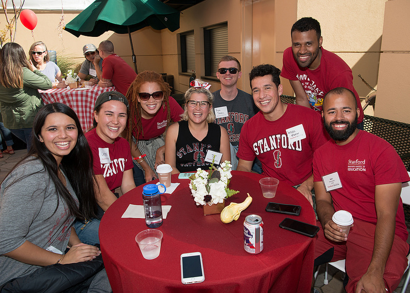 Photo of a group of Stanford alumni sitting at a round table posing for the camera.